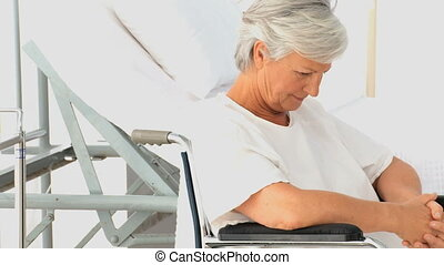 Woman in a wheelchair thinking at the hospital