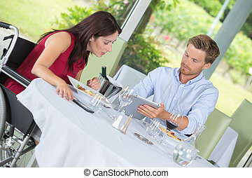 woman in a wheelchair with husband in restaurant