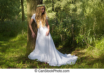 Woman in a white dress and a wreath is standing near a tree