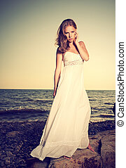 woman in a white dress on the beach by the sea