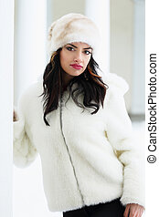 Woman in a white fur coat and hat