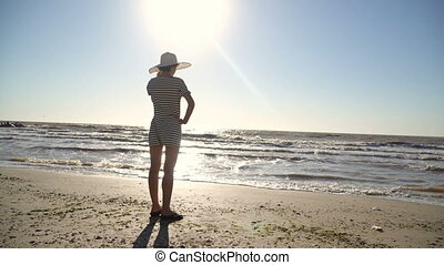 woman in a white hat is standing on the seashore.