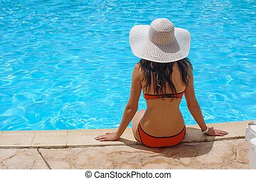 woman in a white hat sits at edge of the pool