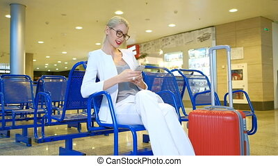 Woman in a white suit sitting in the waiting room with the phone.