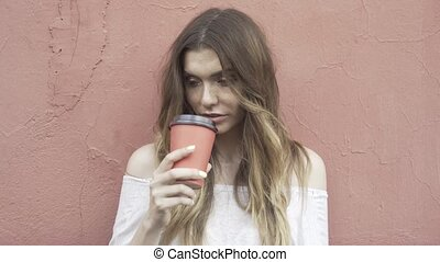 Woman in a white sweater is drinking a coffee to go and looking to the camera