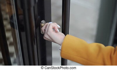 Woman in a yellow coat opens the door of a cafe with a key.