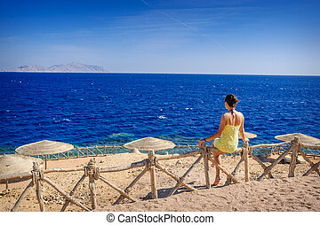 woman in a yellow dress sitting on a fence on the beach and looking at sea