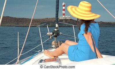 Woman in a yellow hat and blue dress girl rests aboard a...