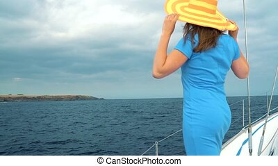 Woman in a yellow hat and blue dress girl rests aboard a yacht on summer season at ocean