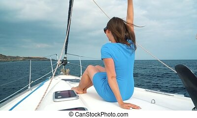 Woman in a yellow hat and blue dress rests aboard a yacht...