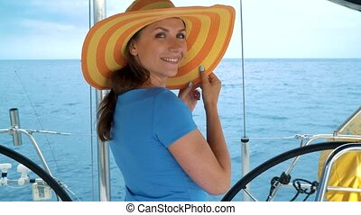Woman in a yellow hat and blue dress standing and smiling on yacht on summer season at ocean