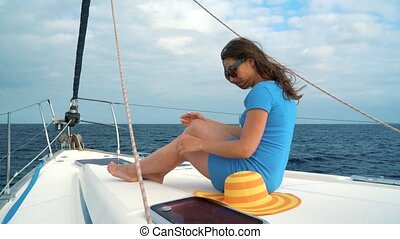 Woman in a yellow hat and blue dress waving hair and smiling on yacht on summer season at ocean