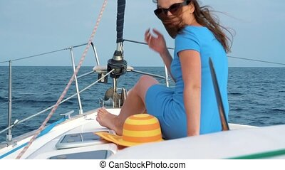 Woman in a yellow hat and blue dress waving hair and smiling on yacht on summer season at ocean. Slow motion