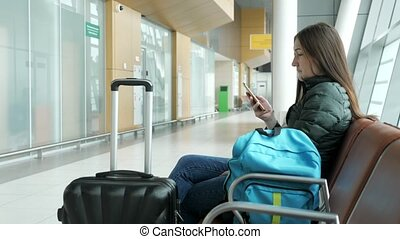 Woman in airport is waiting for her flight, something looking at smartphone.