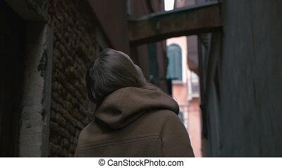 Woman in alleyway looking around