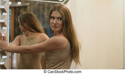 Woman in an elegant brown dress is standing in front of the mirror and smiling