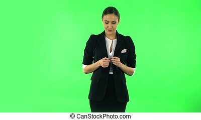 Woman in anticipation of worries, then disappointed and upset. Girl with dark hair wearing a black business suit at green screen at studio.