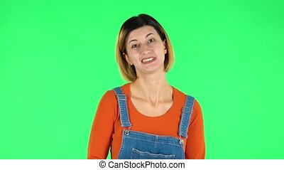 Woman in anticipation of worries, then guilty hides his eyes. Brown-eyed girl with an earring in her ear dressed an orange sweater and denim overalls on a green screen in the studio