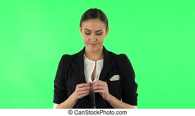 Woman in anticipation of worries, then guilty hides his eyes. Girl with dark hair wearing a black business suit at green screen at studio.