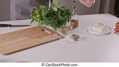Woman in apron preparing to cook a salad of vegetables, cheese, species. On the table, tomatoes, radish, peppers, cheese, greens, olive oil, spices, salt. Tracking motion. Full HD video, 240fps,1080p