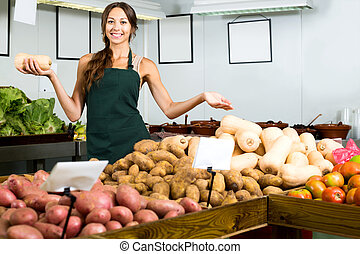 Woman in apron selling small decorative pumpkins