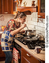 woman in apron stirring soup with kitchen spoon