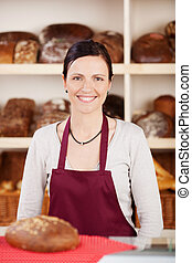 Woman in apron - Smiling woman in apron with big bread on...
