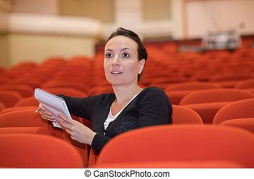 woman in auditorium talking to artists
