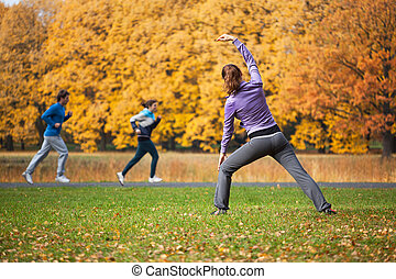 Woman in autumn glade - Athletic woman stretching in autumn ...