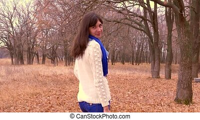woman in autumn leaves in forest in a jacket and a scarf