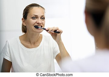 Woman in awhite T-shirt is brushing her teeth in front of mirror. Morning and evening oral hygiene concept