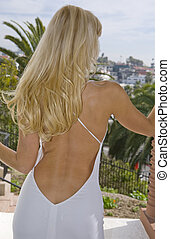 Blonde Woman in Backless Dress overlooking City