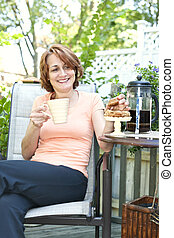 Woman in backyard with coffee and cookies
