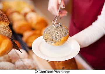 woman in bakery serving bread roll
