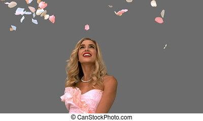 Woman in ballgown admiring petals f