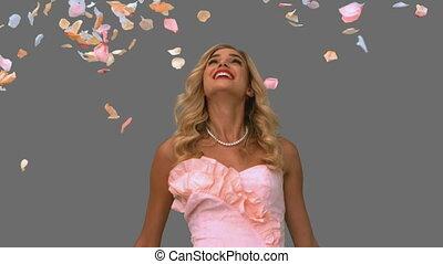 Woman in ballgown standing under petals falling