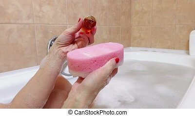 Woman in bath with shampoo bottle and sponge
