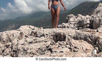 Woman in bathing suit approaching - A woman in bathing suit...