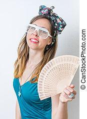 Woman in bathing suit holding hand fan