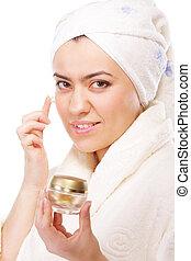 Woman in bathrobe applying moisturizer