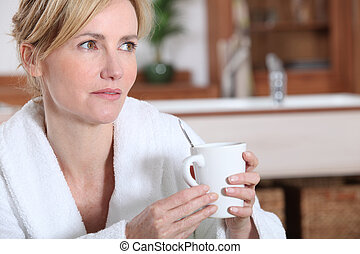 Woman in bathrobe holding cup of coffee