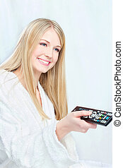 Woman in bathrobe holding remote controller