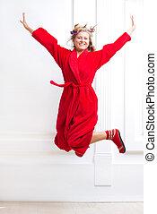 woman in bathrobe jumping joyfully - woman in a red bathrobe...
