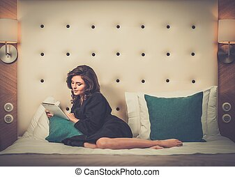 Woman in bathrobe lying on a bed with tablet pc