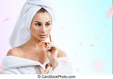 Woman in bathrobe over fresh blue background with swirl petals.