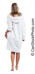 Woman in bathrobe standing back to the camera.