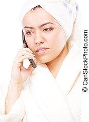Woman in bathrobe talking on phone