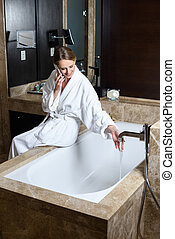 woman in bathrobe using smartphone