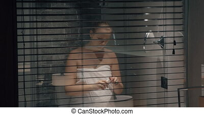 Woman in bathroom applying hand lotion