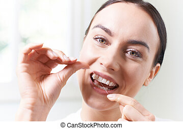 Woman In Bathroom Flossing White Teeth